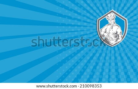 Business card showing illustration of a baker chef cook holding a mixing bowl viewed from front set inside shield crest done in retro woodcut style on isolated background. - stock photo