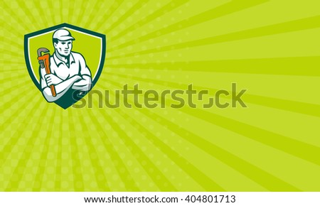 Business card showing illustration of a plumber arms crossed holding monkey wrench viewed from front set inside shield crest on isolated background done in retro style.  - stock photo