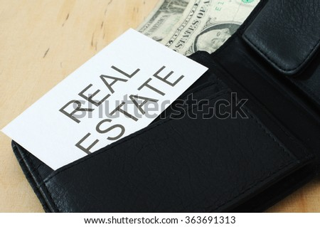 Business card with the sign REAL ESTATE in wallet with dollars   - stock photo