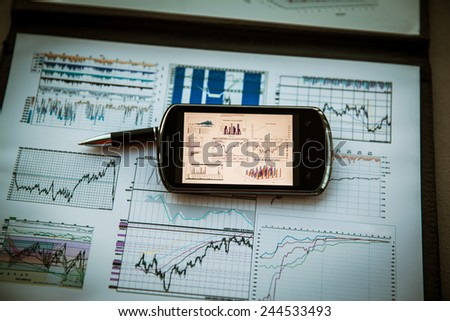 Business chart with smart phone and pen - stock photo