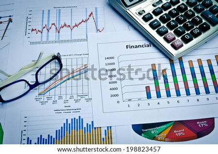 business charts and graphs with eye glass and calculator - stock photo