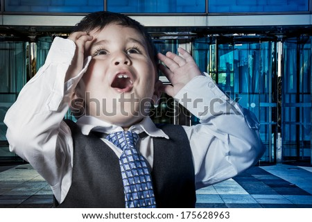 Business, child dressed businessman with hands in his tie and skyscrapers in the background - stock photo