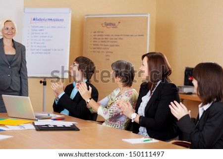 Business class applauding the female lecturer at the end of a training class or presentation - stock photo