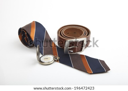 Business clothing accessories with a stylish striped rolled tie, leather belt and old-fashioned silver pocket watch on a white background - stock photo