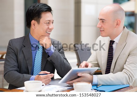 Business co-workers discussing the data and using a touchpad at a cafe on the foreground  - stock photo