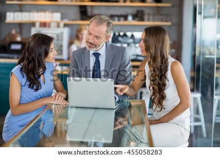 Business colleagues discussing over a laptop in the restaurant - stock photo