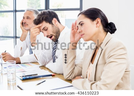 Business colleagues getting bored in a meeting at office - stock photo