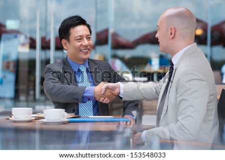 Business colleagues handshaking at a cafe on the foreground - stock photo