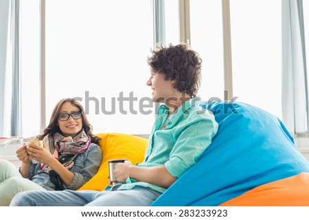 Business colleagues having coffee while relaxing on beanbag chairs in creative office - stock photo