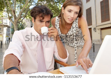 Business colleagues looking at a laptop screen while having a meeting in a coffee shop terrace, outdoors. - stock photo