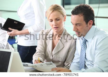 Business colleagues looking at a newspaper - stock photo