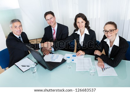 Business colleagues seated around a table in a meeting congratulating one another by shaking hands - stock photo