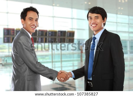 business colleagues shaking hands and smiling to the camera - stock photo