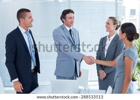 Business colleagues shaking hands in the office - stock photo