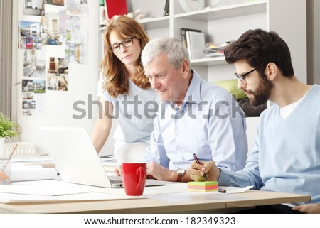 Business colleagues sitting at desk and working on small project.  - stock photo