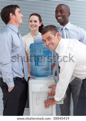 Business colleagues talking around water cooler in workplace - stock photo