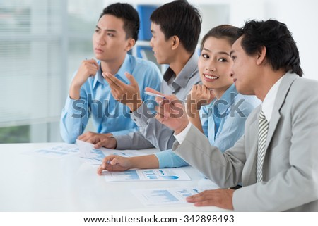 Business colleagues talking when listening to presentation - stock photo