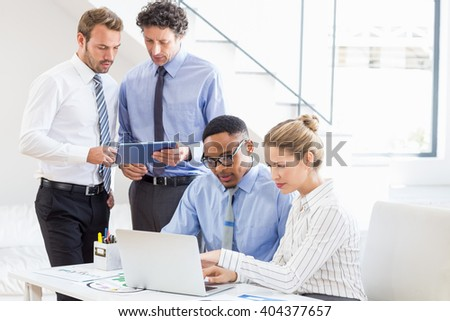 Business colleagues using laptop and digital tablet at desk in office - stock photo