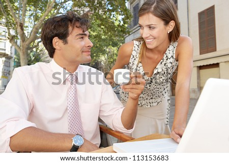 Business colleagues using technology while having a meeting in a coffee shop terrace, outdoors. - stock photo