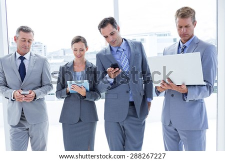 Business colleagues using their multimedia devices in the office - stock photo