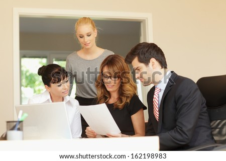 Business colleagues working on a laptop in the office - stock photo