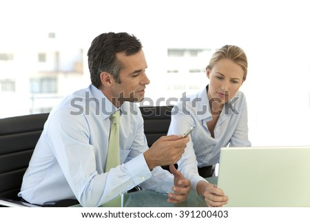 Business colleagues working on laptop  - stock photo
