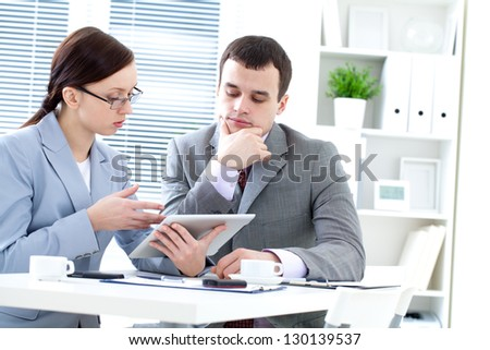 Business colleagues working together and using a digital tablet - stock photo
