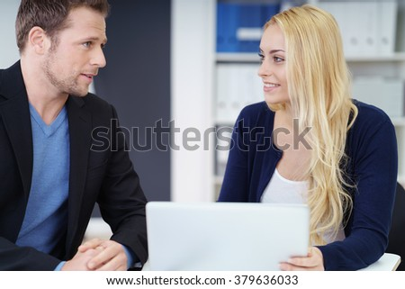 Business colleagues working together in the office using a laptop computer with the young woman listening to the man talking - stock photo