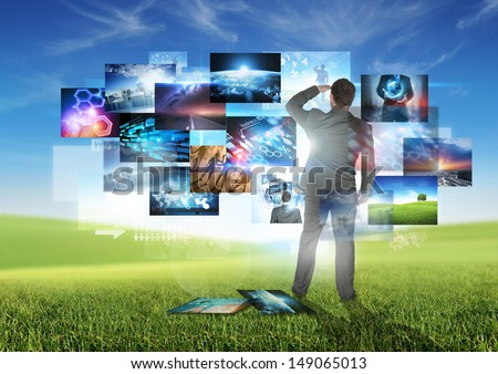 Business Communication - A businessman looking at floating media images. - stock photo