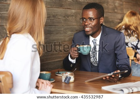 Business communication concept. Two corporate colleagues discussing business ideas using digital tablet. Young African businessman having meeting with his Caucasian female partner at a hotel lobby - stock photo