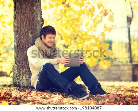 business, communication, modern technology and leisure concept - man with tablet pc in autumn park - stock photo