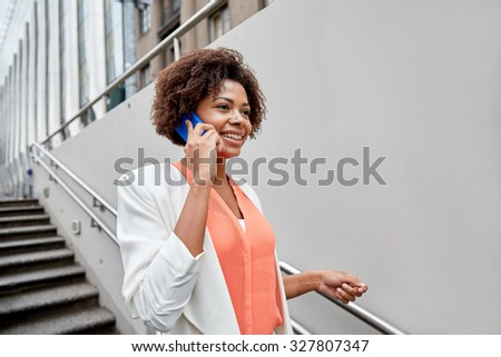 business, communication, technology and people concept - young smiling african american businesswoman calling on smartphone going down stairs into city underpass - stock photo