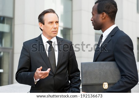 Business communication. Two confident business men talking and gesturing while standing outdoors  - stock photo