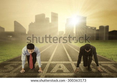 Business competition concept with two businessman kneeling on the start line and ready to compete - stock photo