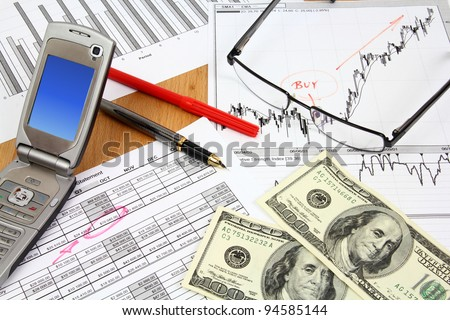 Business composition. Financial analysis - income statement, finance graphs, generic phone, US dollars money and a fountain pen. - stock photo