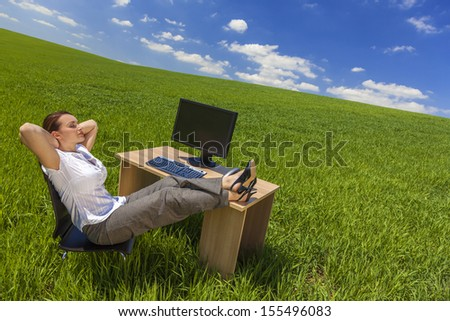 Business concept beautiful woman sitting relaxing day dreaming at desk feet up with computer in a green field with bright blue sky & fluffy white clouds.  - stock photo