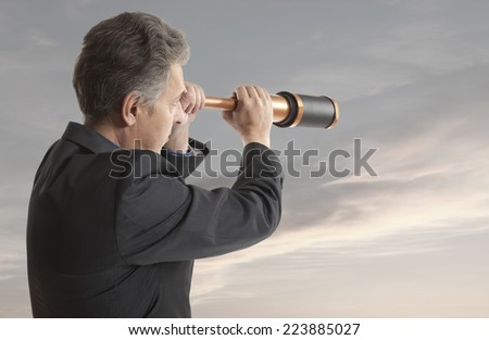 Business concept.  Business man looks through a telescope - stock photo
