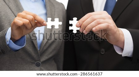 business concept - businessman and businesswoman trying to connect puzzle pieces in office - stock photo