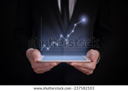 business concept. businessman holding a tablet with the projection of the graph under the screen. financial growth. - stock photo