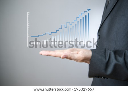 Business concept. Businessman presenting a successful sustainable development on a bar chart on gray background. - stock photo