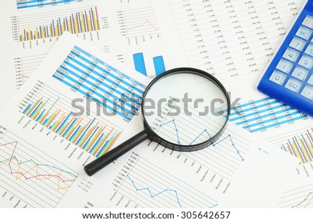 Business concept, calculator and magnifying glass on financial charts and graphs - stock photo
