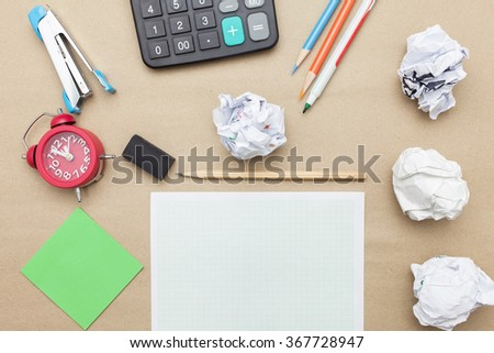 Business concept:Calculator,stapler,red clock,white blank paper,crumpled paper,post it and color pencil,pencil,pen on brown paper background - stock photo