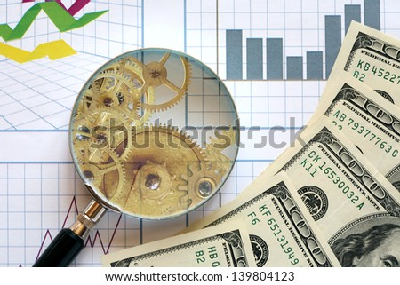 Business concept. Gears inside magnifying glass and money on paper background with chart - stock photo