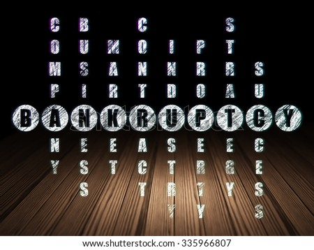 Business concept: Glowing word Bankruptcy in solving Crossword Puzzle in grunge dark room with Wooden Floor, black background - stock photo