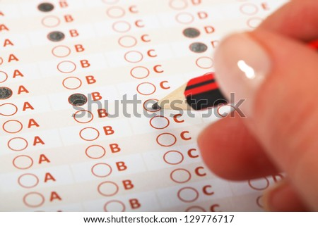 Business Concept - Hand filling in an evaluation form. - stock photo
