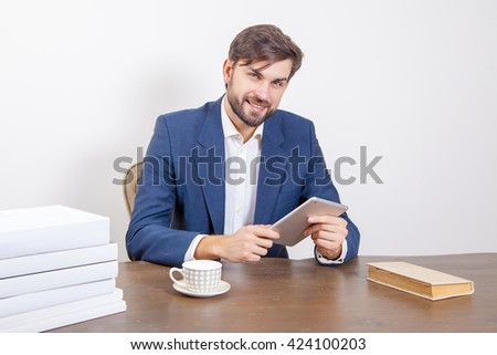 Business concept - handsome man with beard and brown hair and blue suit and tablet pc computer and some books in the office, holding tablet and looking at camera.  Isolated on white background.   - stock photo
