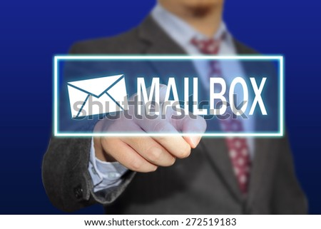 Business concept image of a businessman clicking Mailbox button on virtual screen over blue background - stock photo