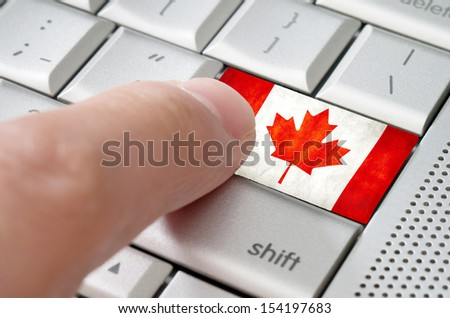 Business concept male finger pressing Canada enter key on metallic keyboard - stock photo