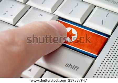 Business concept male finger pressing Nothe Korea enter key on metallic keyboard - stock photo
