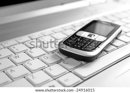 Business concept - mobile phone over laptop keyboard - stock photo